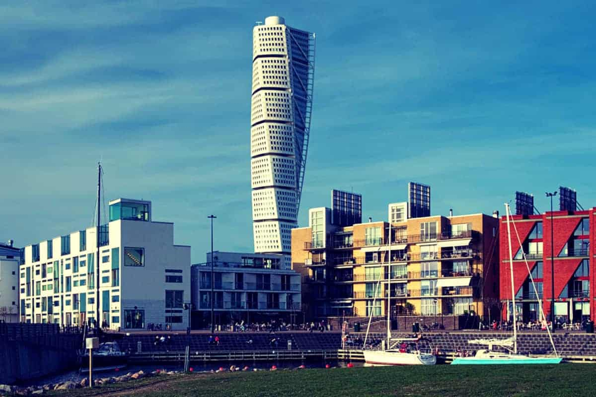 Sail Boats in foreground, Turning Torso Building in middle wiith blue sky Malmo Sweden